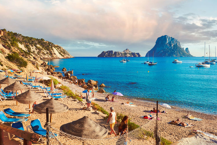 Ibiza Island, Spain - June 12, 2017: People enjoying the summer at Cala d'Hort beach. Cala d'Hort in summer is extremely popular, beach have a fantastic view of the mysterious island of Es Vedra. Ibiza Island, Balearic Islands. Spain Bright Colors Cala D'Hort Coastline Es Vedrá Ibiza Mediterranean Sea Parasols SPAIN Summertime Balearic Islands Beach Beauty In Nature Cloud - Sky Deck Chairs Ibiza Beach Outdoors People Picturesque Rock - Object Rocky Mountains Sandy Beach Sea Sky Sunbathing Sunny Day