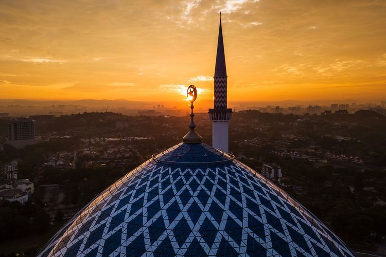 High section of mosque against sky during sunset