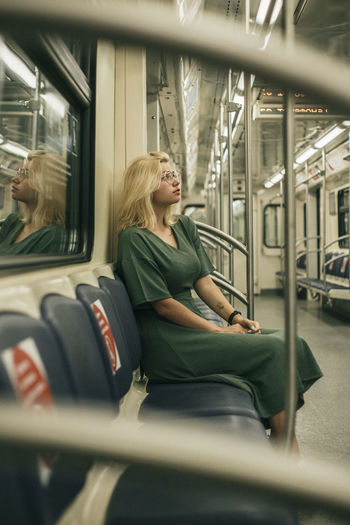 Full length of woman sitting in train