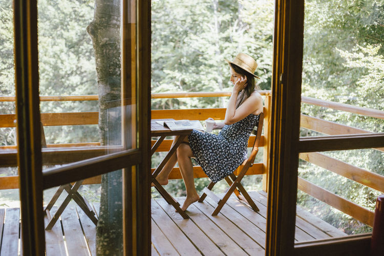 Woman sitting on chair by window