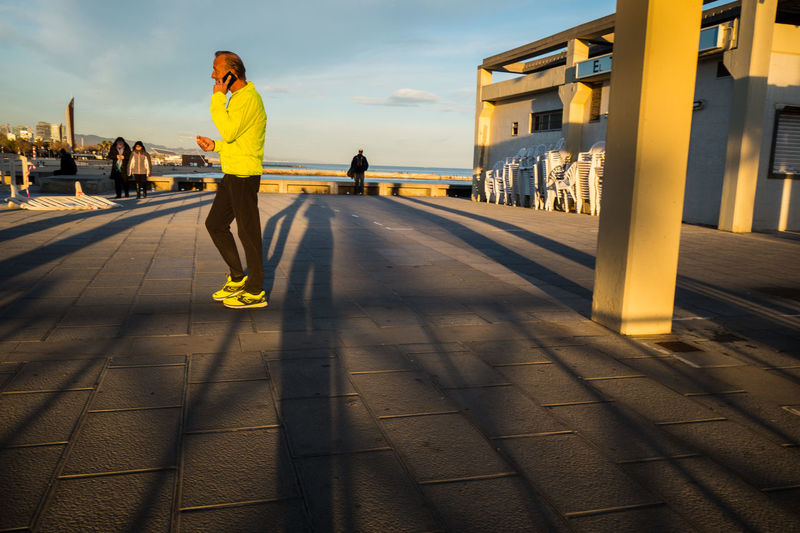 Calling Sportsman Architecture Building Exterior Built Structure Day Full Length Leisure Activity Lifestyles One Person Outdoors People Phone Phoning Real People Runner Shadow Sky Sunlight Telephoning Wireless Technology Yellow Young Adult