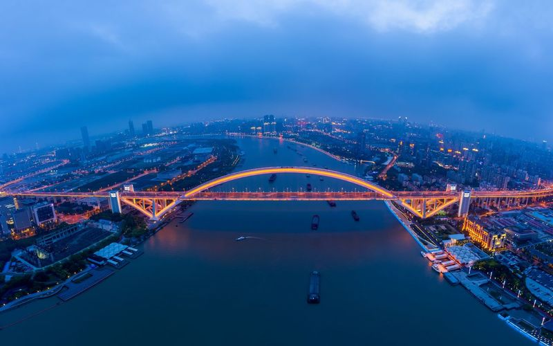Aerial view of illuminated bridge over river at dusk