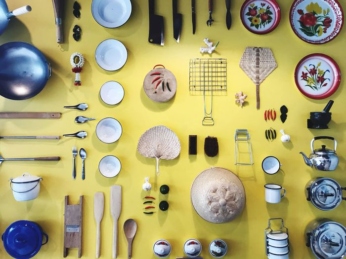 Flat lay of kitchen utensils on yellow background