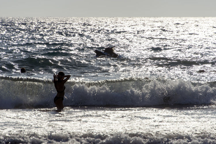 SILHOUETTE OF People playing, swimming in the waves in the island of Patmos, Greece in summer time Beauty In Nature Day Full Length Horizon Horizon Over Water Leisure Activity Lifestyles Men Motion Nature One Person Outdoors Power In Nature Real People Scenics - Nature Sea Sport Surfing Water Wave