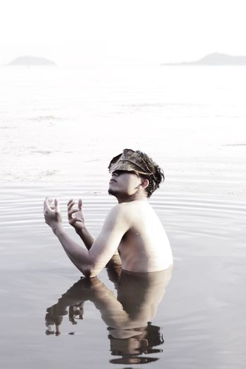 Shirtless man with leaf on face in lake