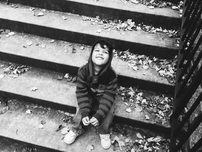 High angle view of boy sitting on steps and making face during autumn