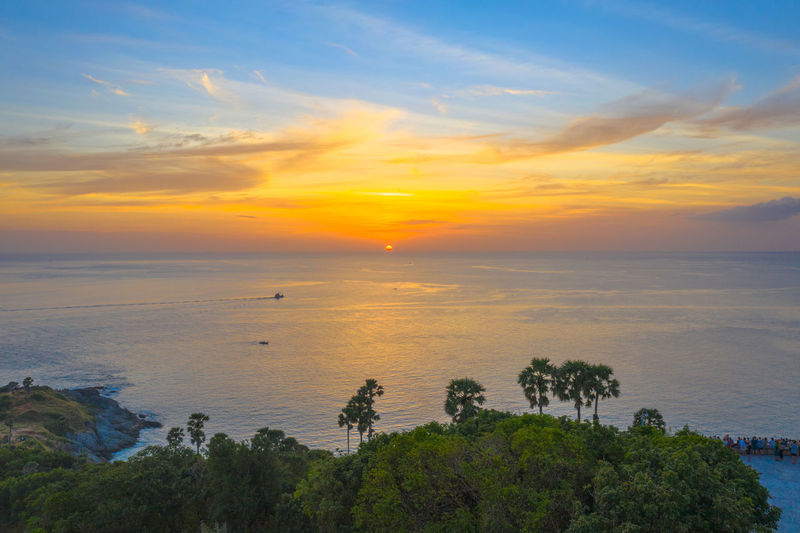 aerial photography sunset at Laem Promthep Cape viewpoint. Promthep cape is the most popular viewpoint in Phuket. the most tourist always come to see sunset at this landmark Phuket,Thailand Promthep, Cape, Dracula, Venice Sugar Palm, Sky Sunset Cloud - Sky Scenics - Nature Beauty In Nature Nature Water Horizon Over Water Travel Tourism Destination Popular, Thanks! Sea Tranquil Scene Tranquility Plant Orange Color Tree Horizon Idyllic No People Land Non-urban Scene Outdoors