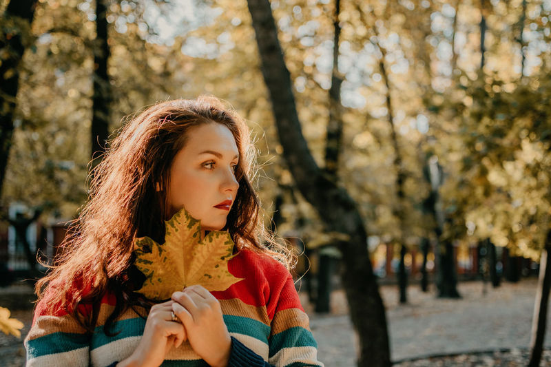 Beautiful woman holding leaf against trees
