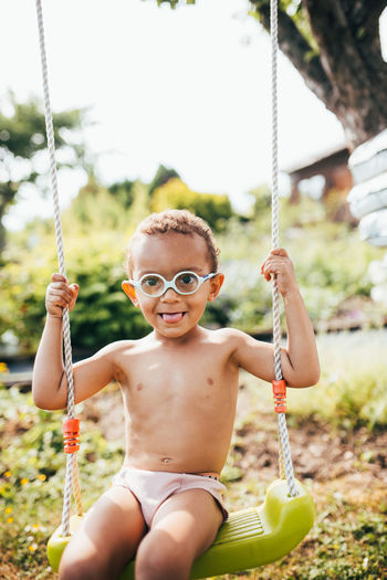 Portrait of shirtless boy sitting on swing against sky