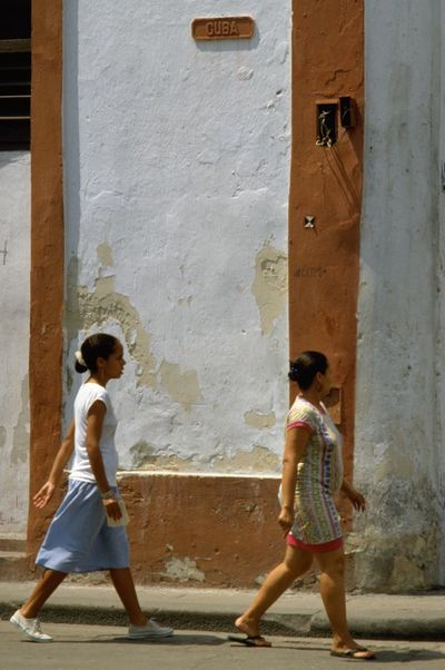 Two Cuban ladies walking down Cuba Calle in Havana, Republic of Cuba. Cuba is the largest island in the Caribbean, and the second-most populous after Hispaniola (Dominican Republic and Haiti). Havana features some wonderful Spanish colonial architecture within its 16th-century core, Old Havana. Paint may be peeling off the walls and street lights don't always work but there are plenty of photo opportunities for street photographers with an eye for the candid shot. http://pics.travelnotes.org Calle Candid Caribbean Casual Cuba Cuban Cubano Havana Islands In The Caribbean Latin America Latinos Michel Guntern Old Town Plain People And Places Simplicity Street Life Street Photography Travel Travel Photography Travel Photos Travel Pics Up Close Street Photography Women Neighborhood Map