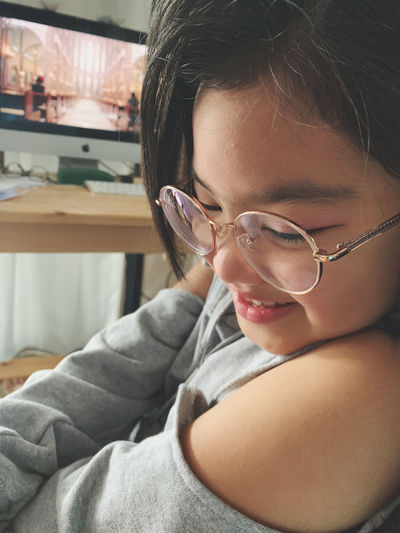 Close-up of cute girl wearing eyeglasses sitting at home