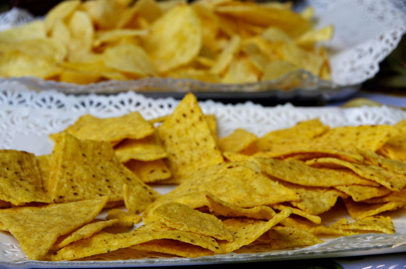 High angle view of tortilla and potato chips served in plate
