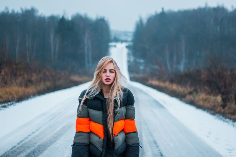 Portrait of young woman standing on road during winter