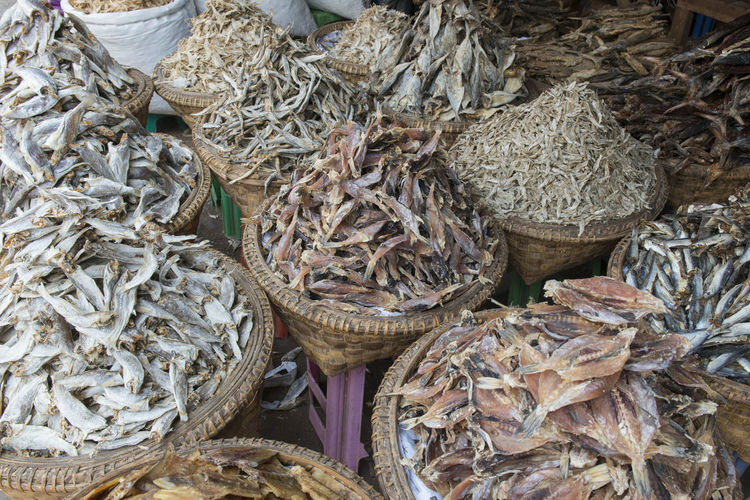High angle view of dried fish in baskets at market for sale