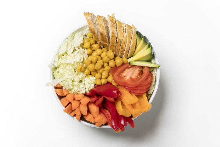 High angle view of chopped vegetables in bowl against white background