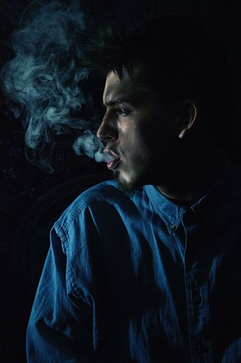 Young man exhaling smoke against black background