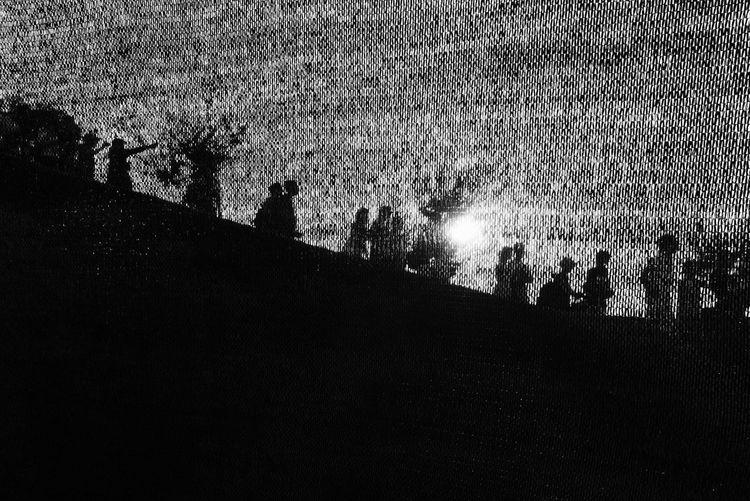 Silhouette people on field against sky