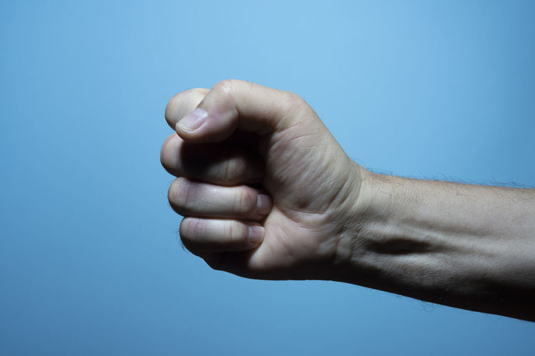Close-up of human hand against blue background