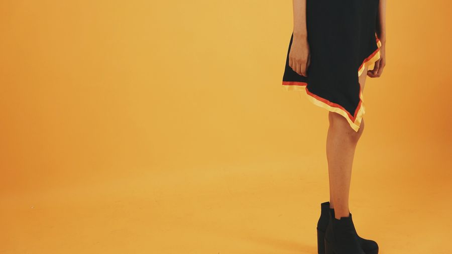 Low Section Of Fashionable Woman Standing Against Orange Background
