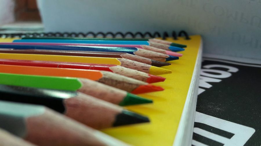 Close-up of colored pencils on spiral notebook