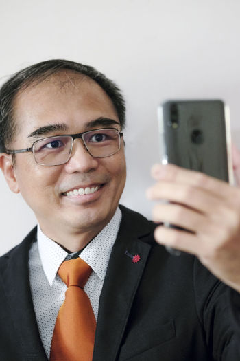 Happy businessman using mobile phone to take selfie Happy Mobile Phone Tech Adult Business Person Businessman East Asian Eyeglasses  Front View Headshot Holding Indoors  Lifestyles Males  Men Menswear One Person People Portrait Smiling Suit Taking Selfies Technology Using Mobile Phone Well-dressed