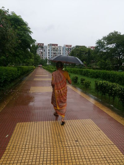 Architecture Built Structure City Day Diminishing Perspective Empty Footpath Grass Growth Long Narrow Nature Outdoors Pathway Plant Rain Rainy Rainy Season Sky The Way Forward Tree Umbrella Vanishing Point Walkway Woman