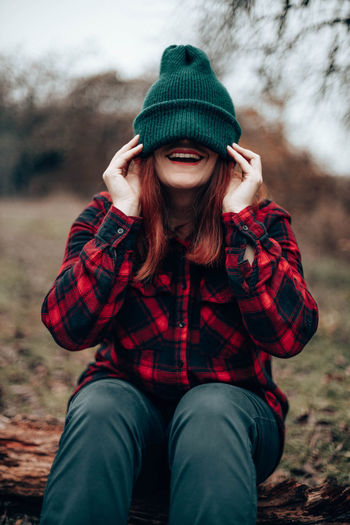 Happy young girl in a green knit cap pulled over her eyes and a plaid shirt in the autumn forest
