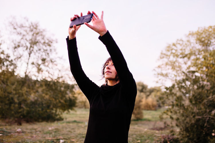 Smiling woman doing selfie while standing at park