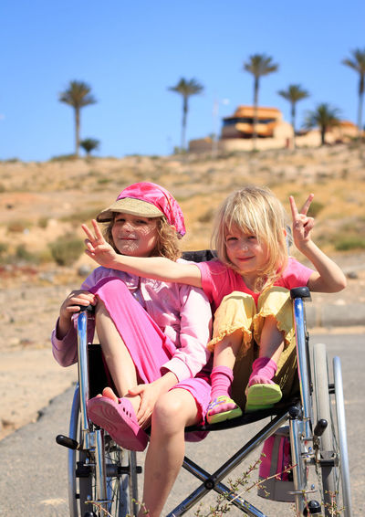 Cute siblings sitting on wheelchair against sky