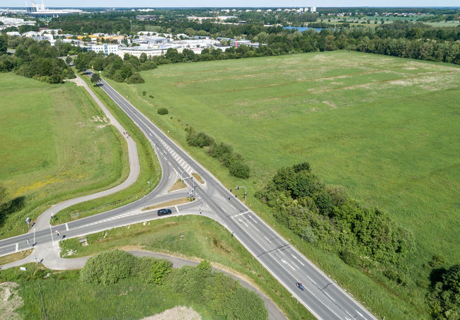 Aerial view of the turn-off of a ring road with the houses of the dominion in the background Country Road Drone Landscape Aerial View Car City Day Drive Environment Green Color High Angle View Highway Junctionsquare Land Land Vehicle Landscape Mode Of Transportation Motor Vehicle Nature No People Outdoors Plant Road Scenics - Nature Transportation Tree