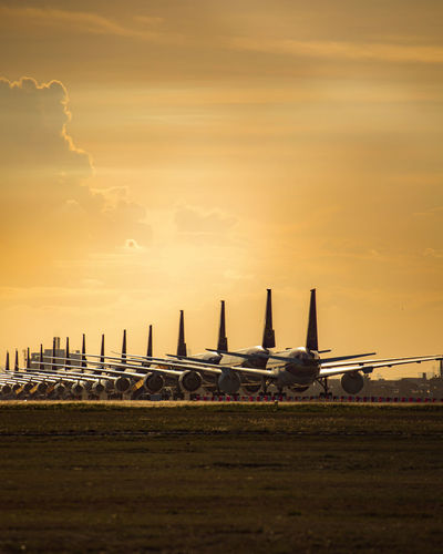 Airplane on airport runway against sky during sunset