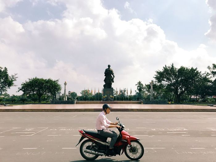 Loner - Sky Transportation Mode Of Transport Cloud - Sky Riding Sitting Tree Outdoors Day Real People Land Vehicle Motorcycle Men One Person Architecture Streetphotography Wide Shot Vietnam Alone Empty Road Empty Transportation My Year My View Eye4photography  EyeEm Best Shots