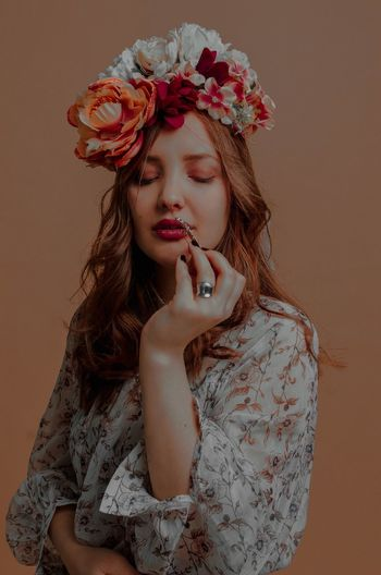 Young woman wearing flowers against colored background