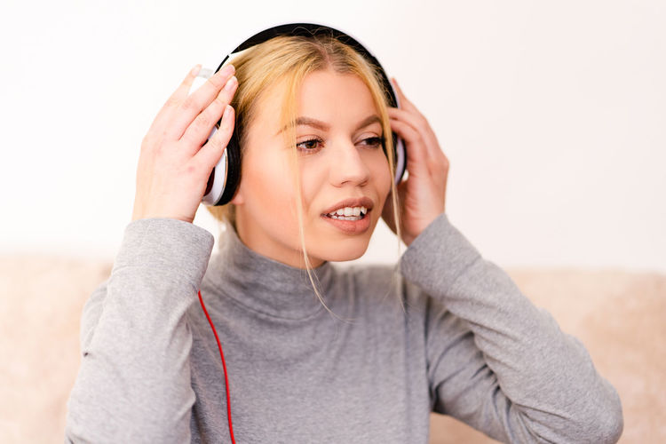 Listening Headphones One Person Technology Indoors  Music Front View Casual Clothing Portrait Young Adult Emotion Headshot Young Women Happiness Connection Smiling Lifestyles Communication Leisure Activity Wireless Technology