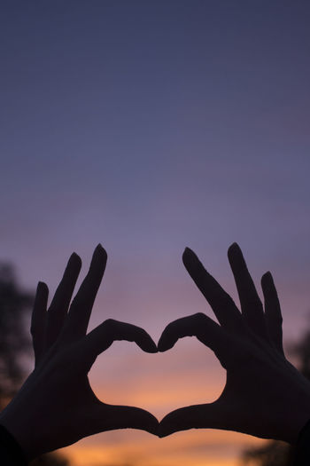 Silhouette of hand making heart shape against sky during sunset