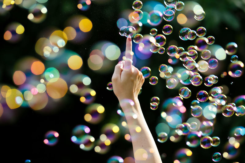 Cropped hand of woman touching bubbles