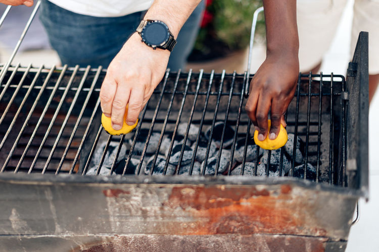 Multiethnic friends doing barbecue meal outdoors at backyard - people cleaning grill using lemon