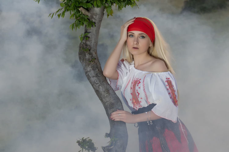 Portrait Of Beautiful Young Woman Standing By Tree Trunk In Smoky Weather