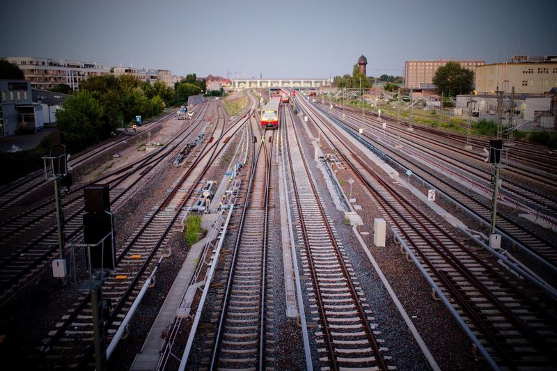 High angle view of train on railroad tracks in city against sky