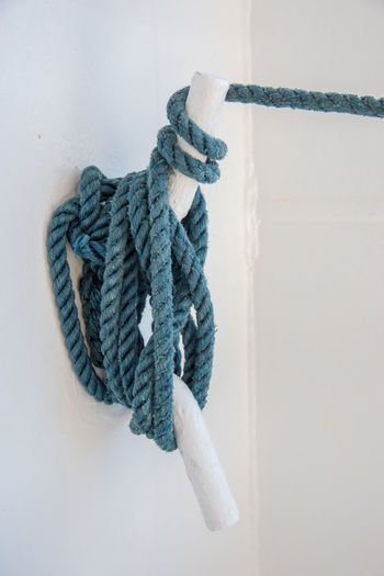 Nautical rope tie down with white background. Lines Nautical Equipment Rope Blue Boat Cleat Cleat Hitch Closeup Hitch Knot Knotted Knotted Rope Nautical Nautical Cleat Nautical Rope Nautical Ship Rope Nautical Theme Rope And Cleat Secure Tie Tie Down Tied Tied Down White Background Wrapped