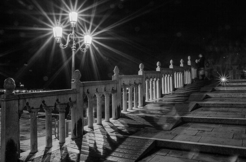 Illuminated lamp post by railing at steps against sky
