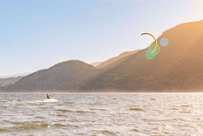 PENTICTON, BRITISH COLUMBIA, CANADA - OCTOBER 24, 2017 a kiteboarder enjoys sailing across Skaha Lake near Sudbury Beach on a windy autumn evening. This area is a very popular location for the sport Adrenaline Autumn Beautiful British Columbia, Canada Kite October Travel Action Adventure Editorial  Evening Extreme Sport Kiteboarding Kitesurfing Landscape Man Mountains person Skaha Lake South Okanagan Speed Sport Sunset Sunshine Tourism