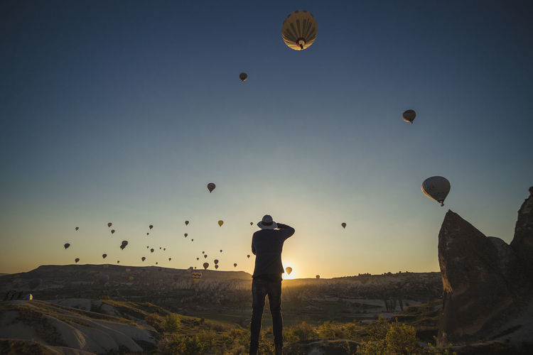 Beauty In Nature Cappadocia Cappadocia Ballon Cappadocia/Turkey Flying Hot Air Balloon Hot Air Balloons Landscape Leisure Activity Lifestyles Men Mid-air Motion Nature One Person Outdoors Photography Themes Real People Shadows & Lights Silhouette Sky Standing Sunrise Sunset Turkey