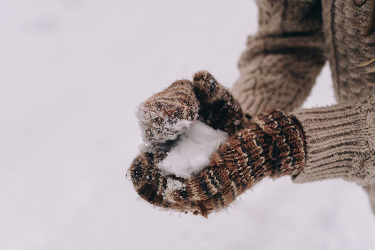 Close-up of human hand holding snow