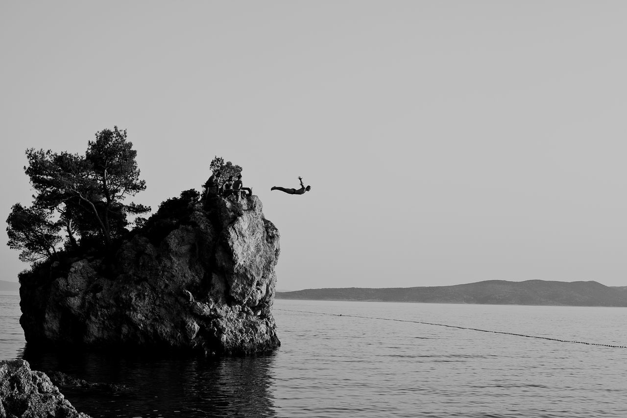 Man Jumping In Sea Through Rock Against Clear Sky