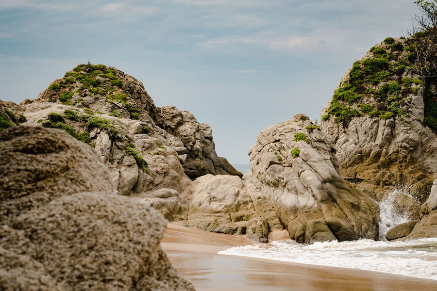Rocks and Beach at Huatulco, Mexico Huatulco, Oaxaca, México Arid Climate Beauty In Nature Cliff Day Eroded Formation Geology Land Mountain Nature No People Non-urban Scene Outdoors Pacific Ocean Rock Rock - Object Rock Formation Scenics - Nature Sky Solid Tranquil Scene Tranquility Water