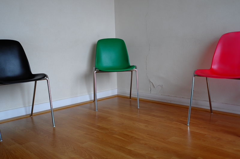 Colorful chairs on hardwood floor in room