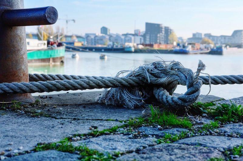 Close-up of rope tied on bollard at harbor
