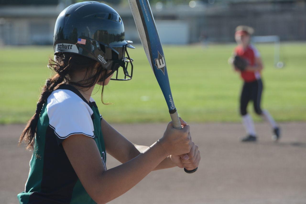 Girls playing baseball on field