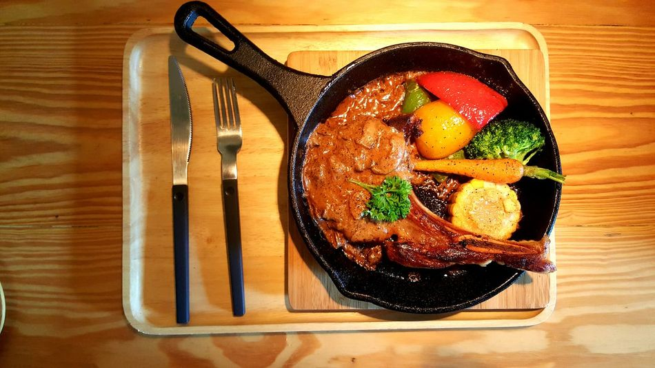Pork chop on hot pan Hot Pan Grilled Food Ready-to-eat Porkchop Steaks Dinner Wooden Table Warm Tone Knife Fork Home Meal Corn Bell Pepper Baby Carrots Mushroom Sauce Broccoli Recipe For One EyeEmNewHere